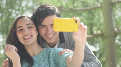 stock-footage-young-couple-taking-self-portrait-on-smartphone